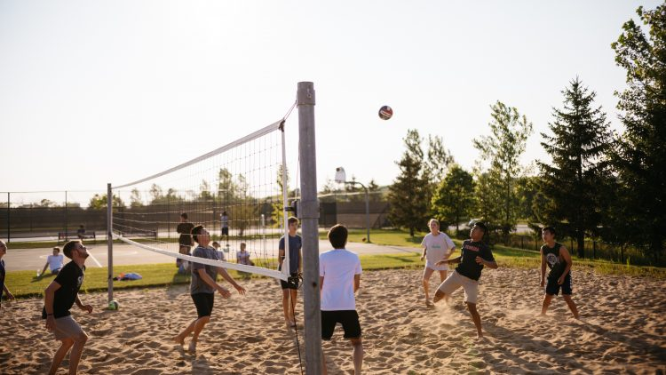 men playing volleyball near pine trees