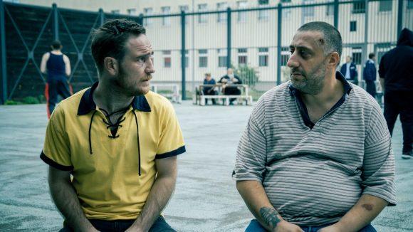 zwei Männer nebeneinander auf einer Bank