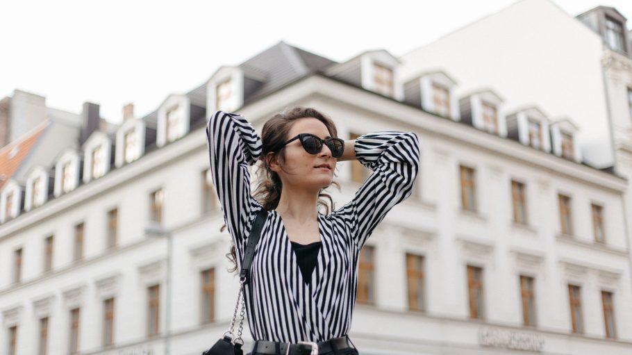 Frau mit Sonnenbrille und Hände hinter dem Kopf verschränkt