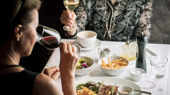 Zwei Frauen trinken Wein am Tisch und essen