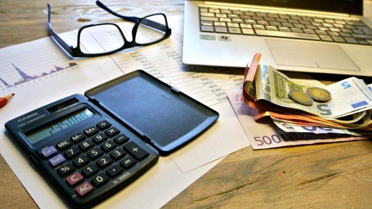 Taschenrechner mit Geld am Tisch