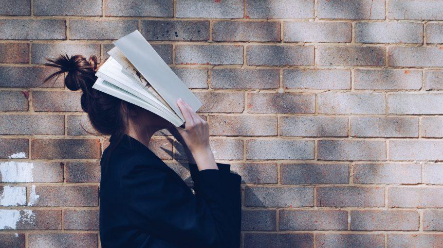 Frau mit Buch vor dem Gesicht
