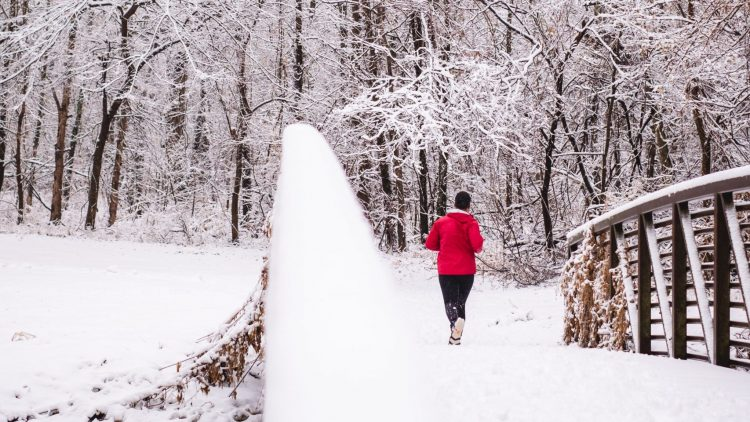 person in red jacket walking on snow covered pathway