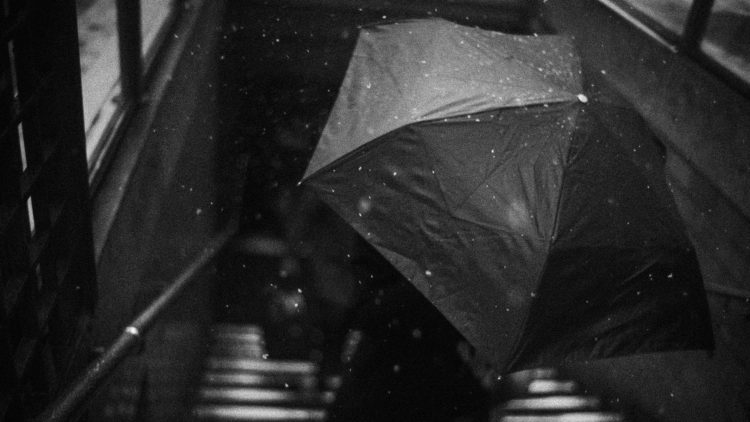 grayscale photography of person holding umbrella on downstair