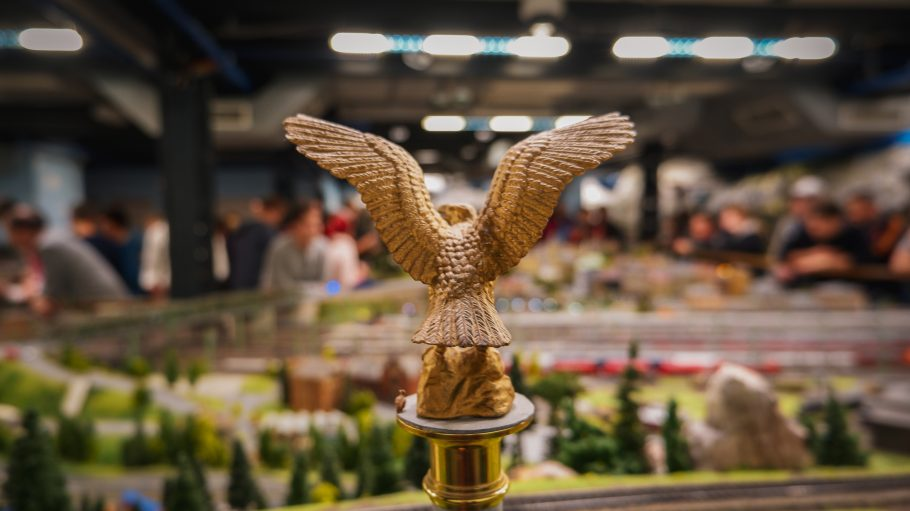 gold-colored eagle figurine on post near people