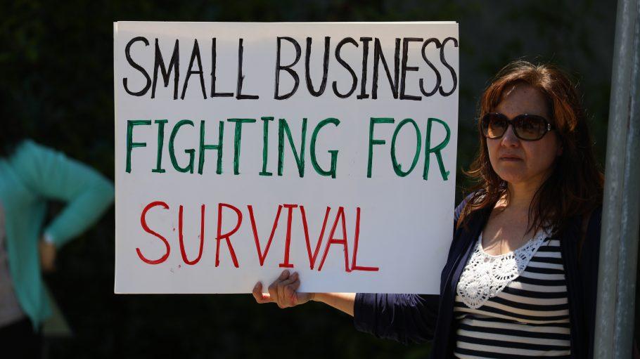woman in black cardigan holding happy birthday signage