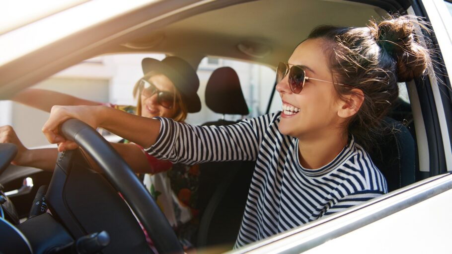 Two attractive young girlfriends wearing sunglasses talking and laughing together while driving in a car through the city on a sunny day