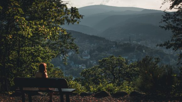 man sitting on bench looking at the mountains during daytime