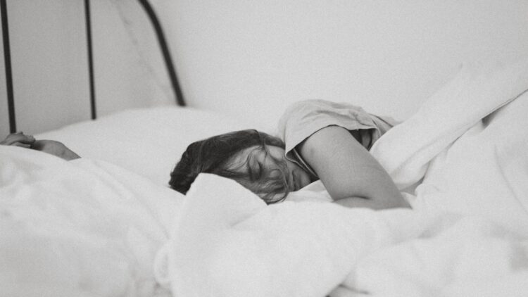 grayscale photo of sleeping woman lying on bed