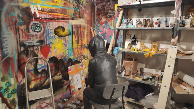 Figur sitzt auf Stuhl, Graffiti im Hintergrund