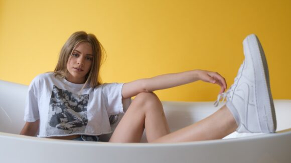 woman in white and blue floral shirt and white shorts sitting on bathtub
