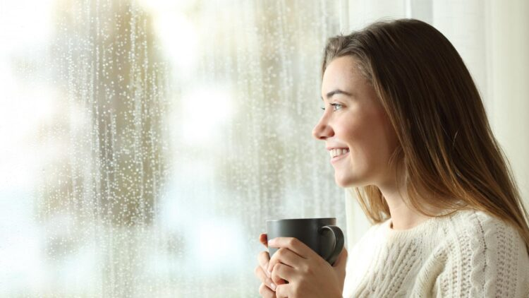 Frau mit Tasse am Fenster