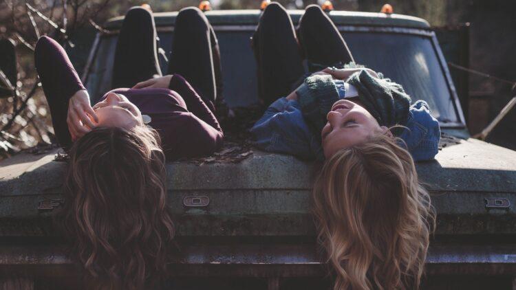 Mädchen auf Auto liegend