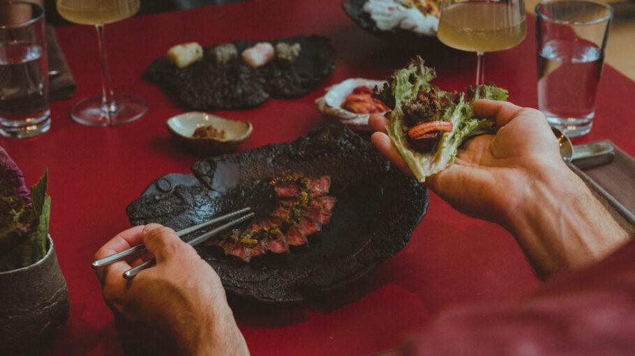 """Einmal wickeln, bitte! Das kurz gebratene Rumpsteak kannst du """"selbst gestalten"""", mit Salatblättern, Reis, Sesamblättern und Kimchi."""