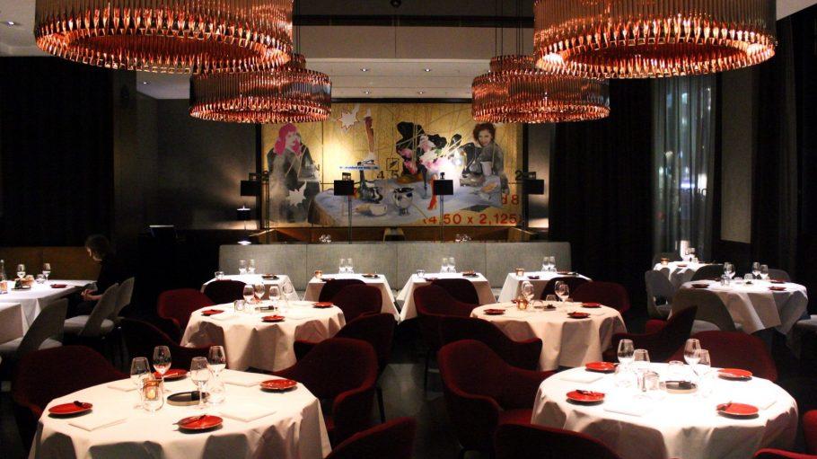 Kupferlampenhängen über weiß gedeckten Tischen und dunkelroten Sesseln im Restaurant Le Faubourg. Das Bild an der Wand: Überbleibsel vom Design vor dem Makeover 2014.