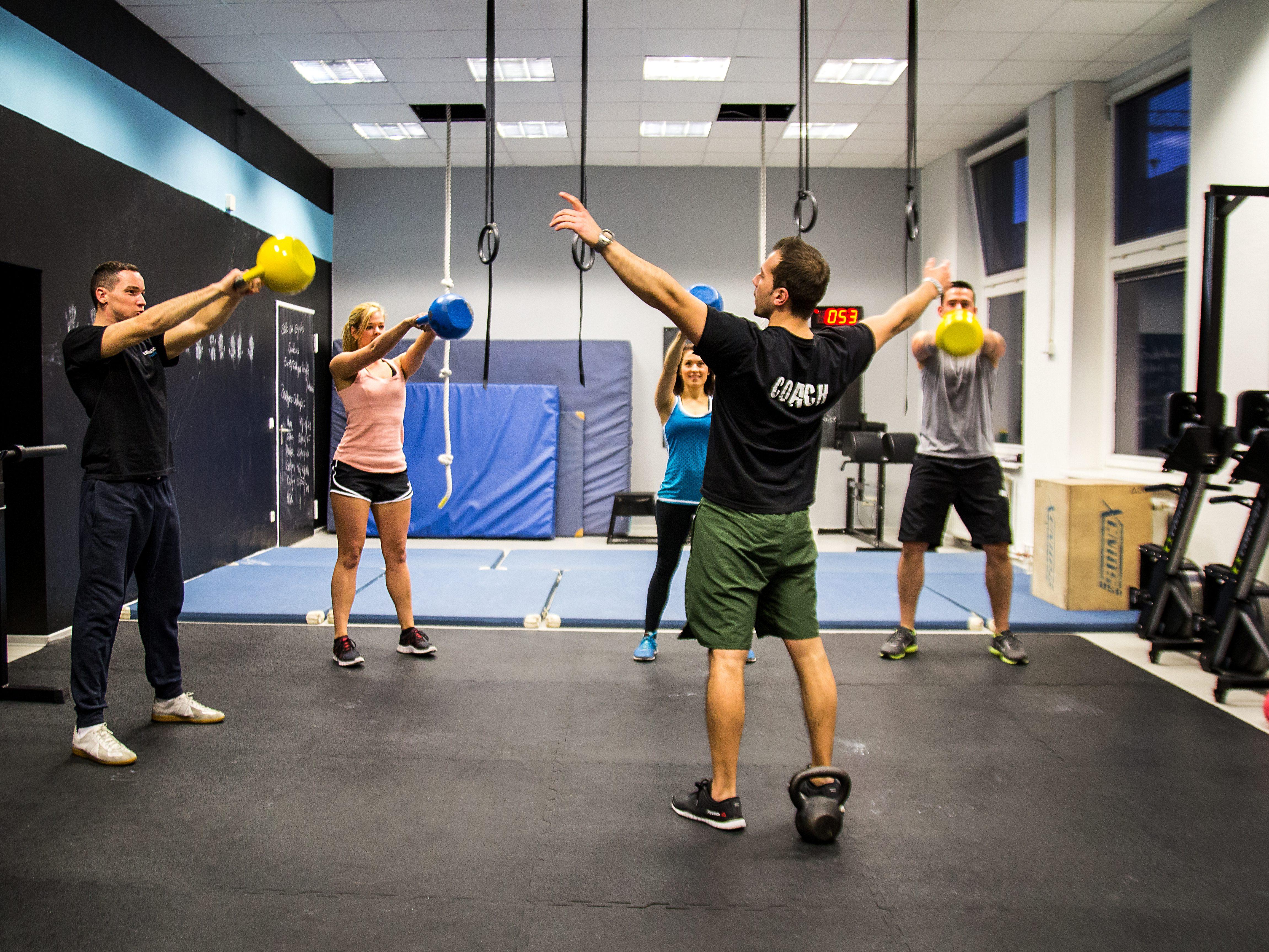 Bei der Sportart Crossfit arbeitet man unter anderem mit Kettlebells, die hier in gelb und blau in den Händen der Teilnehmer zu sehen sind.