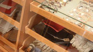 Accessoires wie Brillen, Handschuhe, Taschen & Co. liegen im Regal.